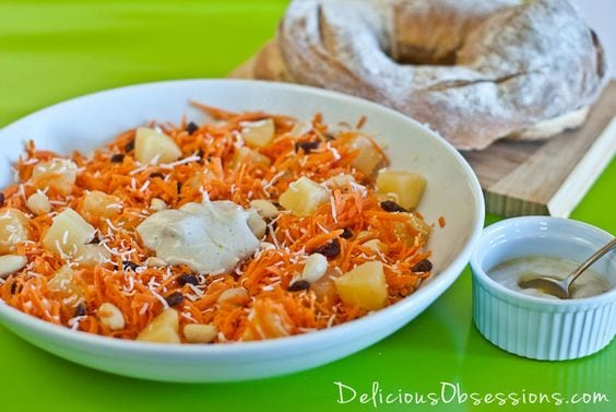 Carrot salad with pineapple, coconut, walnuts in white bowl with side of sauce and bread on cutting board with white text overlay