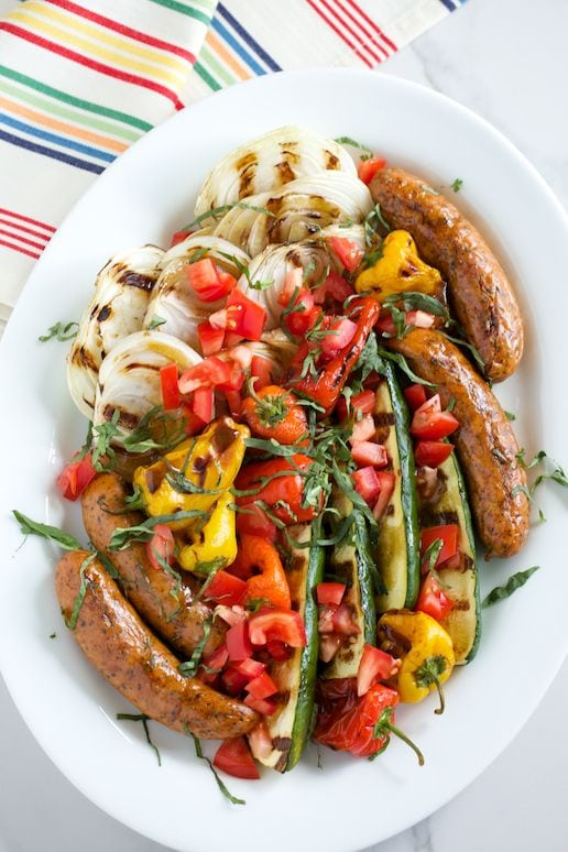 Grilled Italian sausage with onions, zucchini, peppers on a white plate with striped napkin