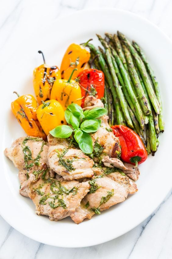 Lemon Basil Grilled Chicken with grilled peppers and asparagus on a white plate