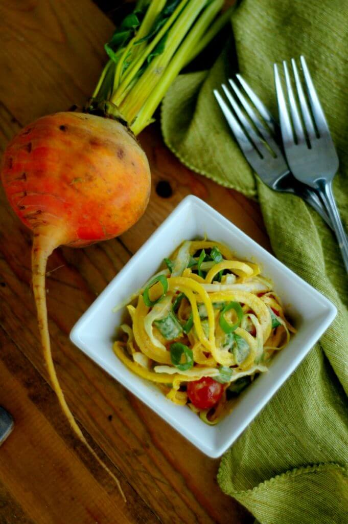 Golden beet slaw in white bowl with forks and green table cloth