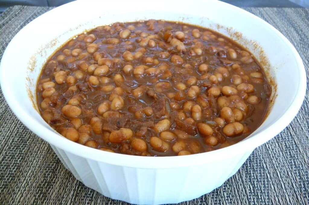 Baked beans in white bowl on placemat