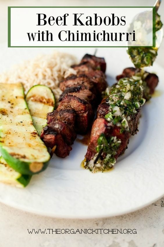 Beef kabobs with chimichurri, grilled zucchini, rice on a white plate with black text overlay