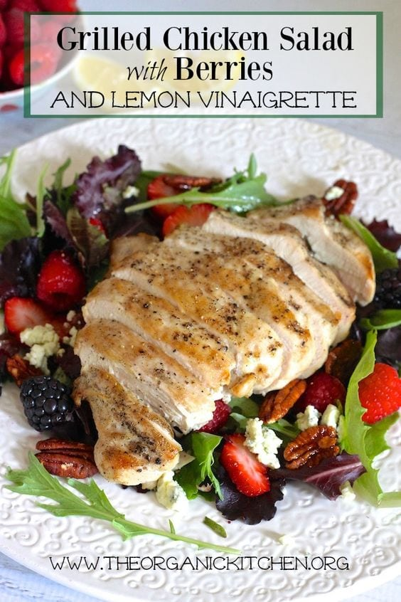 Grilled chicken salad with berries and lemon vinaigrette on white plate with black text overlay