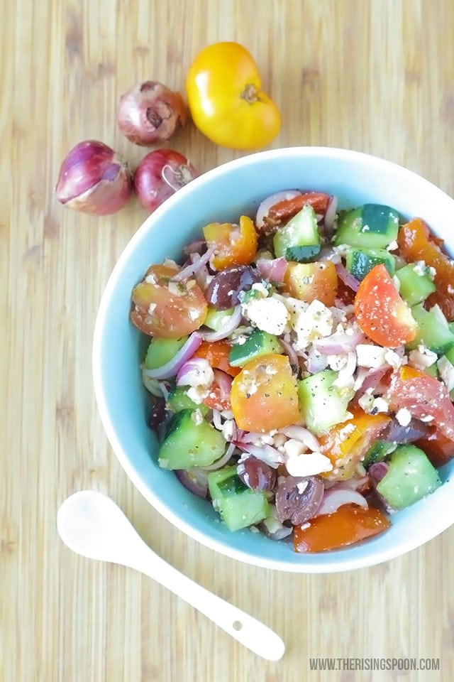 Greek salad with tomatoes, cucumbers and onions in blue bowl with white spoon and wood cutting board