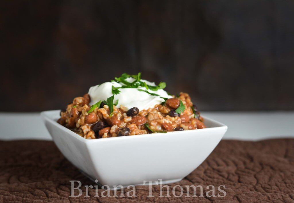 white bowl of beans and rice topped with sour cream
