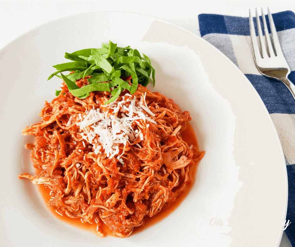 red shredded chicken in white bowl