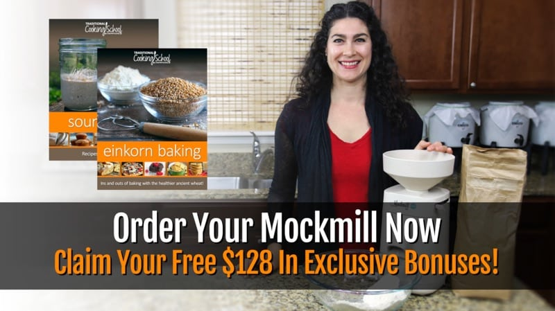 "Woman smiling in her kitchen next to the Mockmill home stone grain mill. Text overlay says ""Order Your Mockmill Now & Claim Your Free $128 In Exclusive Bonuses!"""