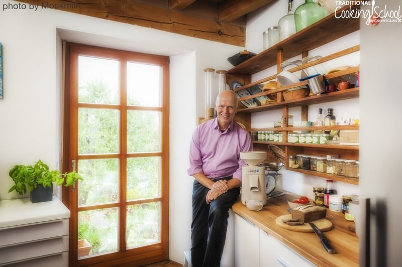 man in a beautiful kitchen with open shelving with a Mockmill, the best affordable home grain mill, next to him on the counter