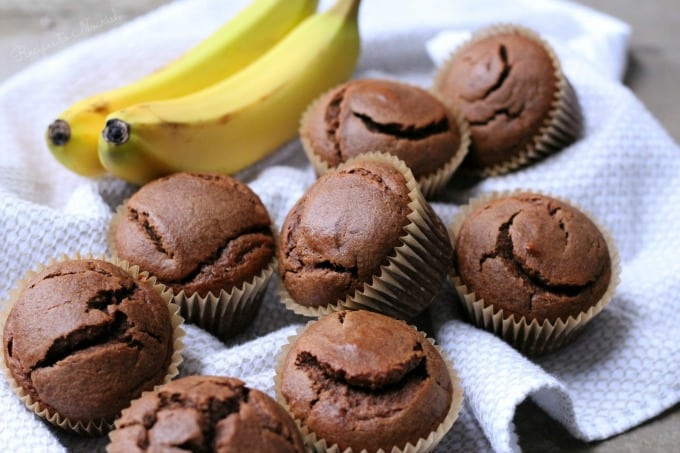 chocolate muffins laying on a white towel with bananas