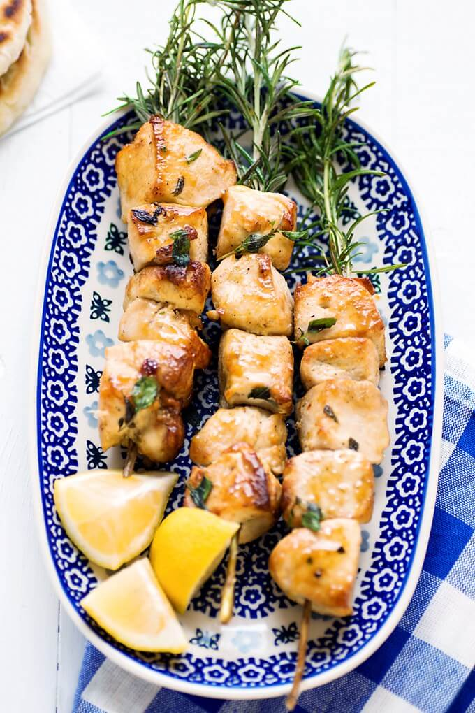 Mediterranean chicken skewers with rosemary and lemon wedges on blue plate with checkered napkin