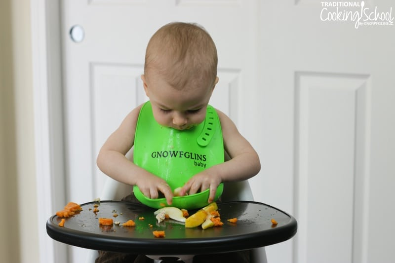 happy gnowfglins baby digging food out of his green bib