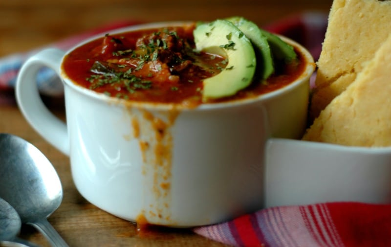 white mug with red soup dripping down the sides garnished with avocado slices