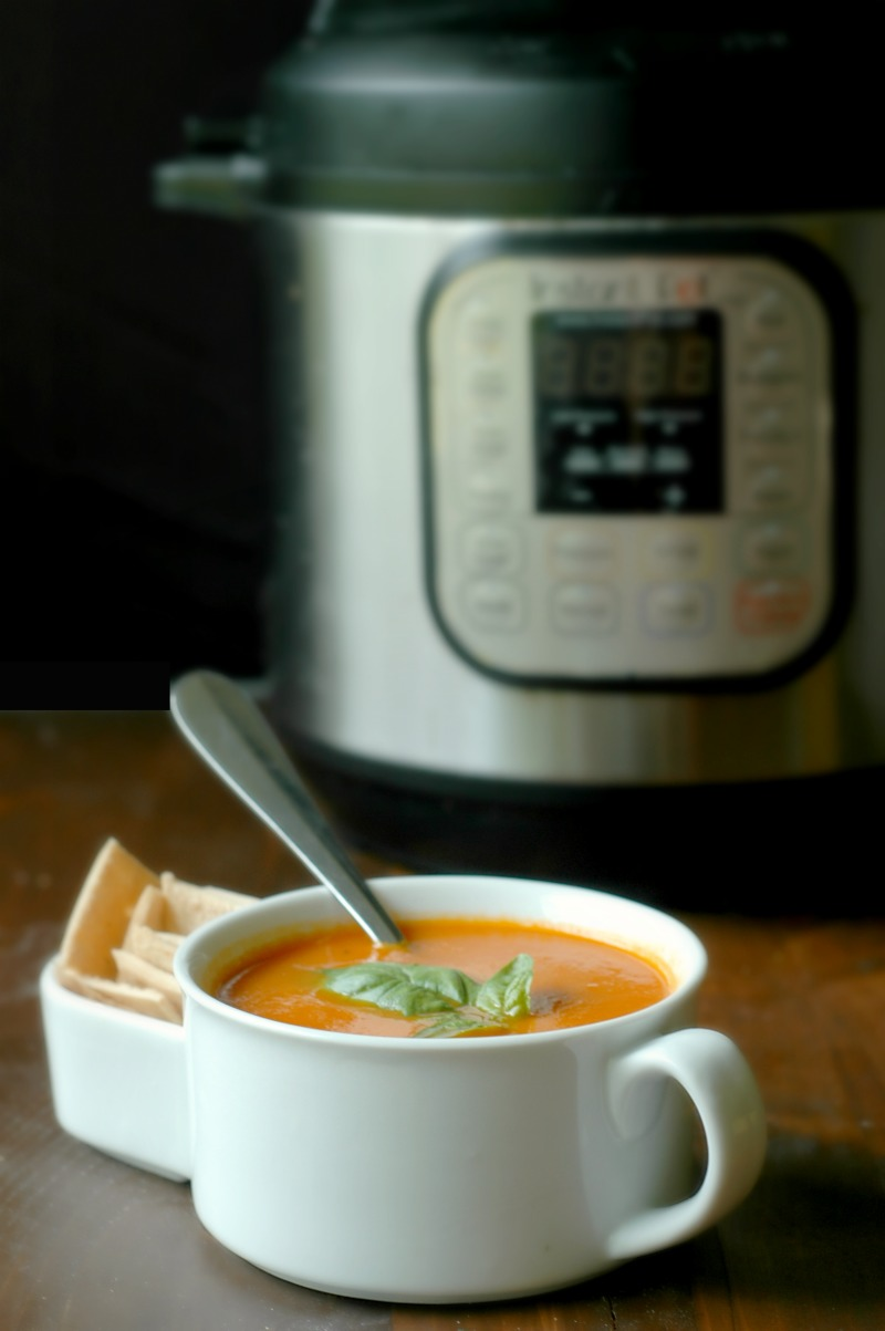 white mug of tomato soup with instant pot in the background