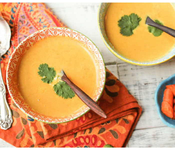 colorful bowls of orange soup garnished with cilantro