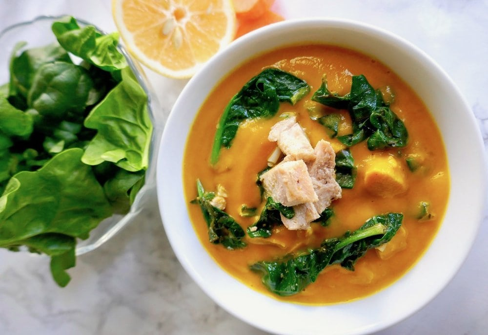 orange soup with spinach and chunks of chicken