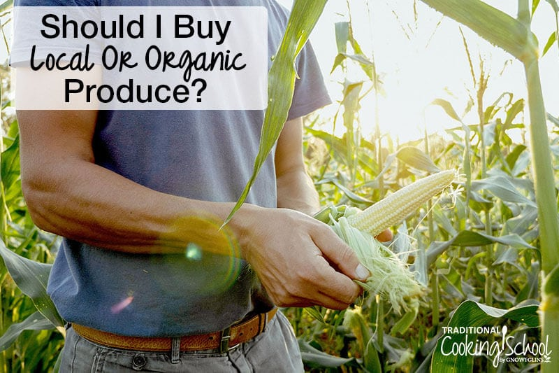 male farmer in a field of corn shucking corn cob with text overlay should i buy local or organic produce