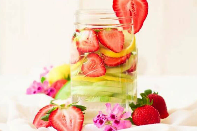 refreshing jar of water with fresh strawberries, cucumbers, lemons surrounded by fresh fruit and flowers
