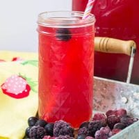 probiotic mixed berry switchel in a glass with a pink-striped paper straw