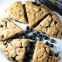 plate of six blueberry scones with blueberries and lavender scattered around