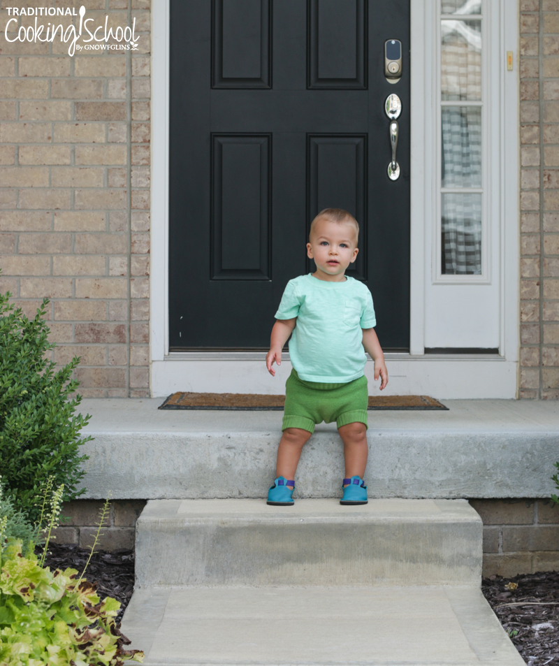 toddler standing on front porch steps while wearing bright blue leather moccasins