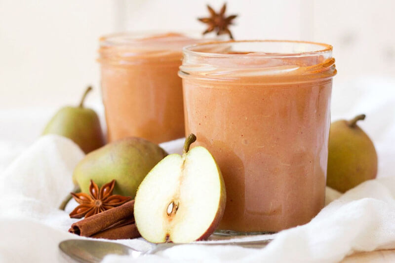 glass jars of apple sauce with surrounding pears and spices