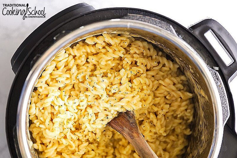 pressure cooker full of macaroni and cheese with a wooden spoon stirring it