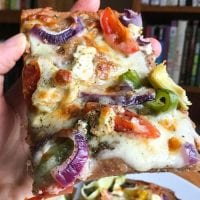 hand holding up a piece of mediterranean sourdough pizza topped with cheeses, tomatoes, bell peppers, onions, and artichoke hearts