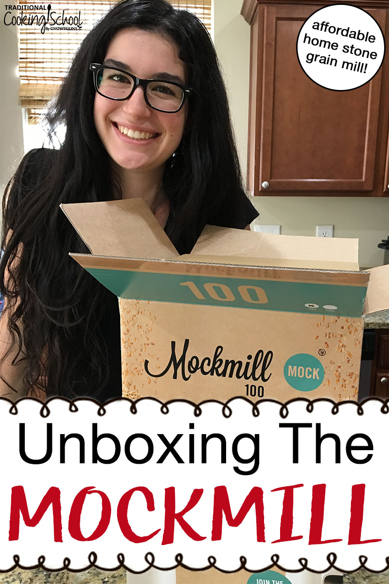 "brunette smiles next to an open box with home stone grain mill inside, with text overlay: ""Unboxing The Mockmill"""