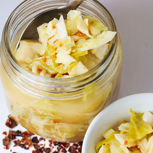 silver spoon scooping sauerkraut with rose hips out of a glass jar into a waiting white ceramic bowl