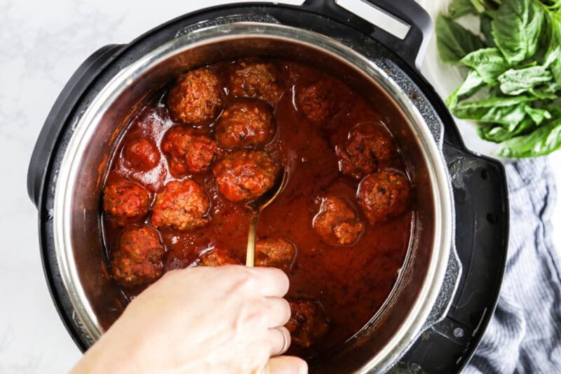hand scooping a spoon into an instant pot full delicious spaghetti sauce and meatballs