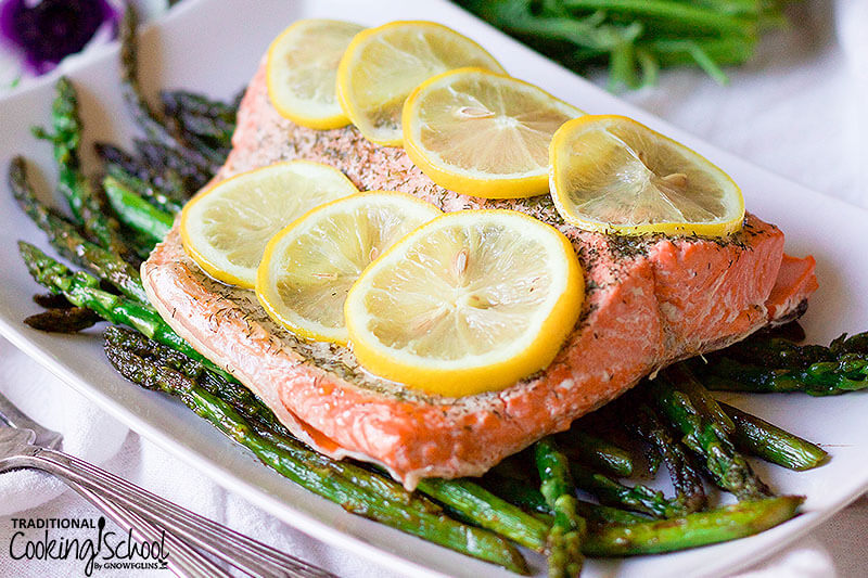salmon filet topped with lemon slices on a bed of asparagus