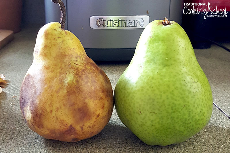 one very ripe pear with bruised spots and one bright green, unripe pear