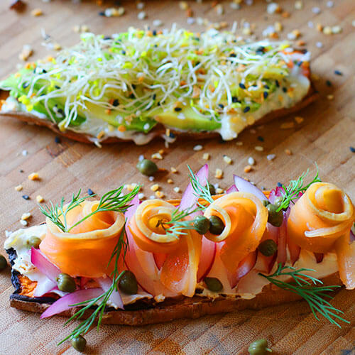 two slices of sweet potato toast made in up in different ways, one with smoke salmon and cream cheese, the other with avocado and sprouts