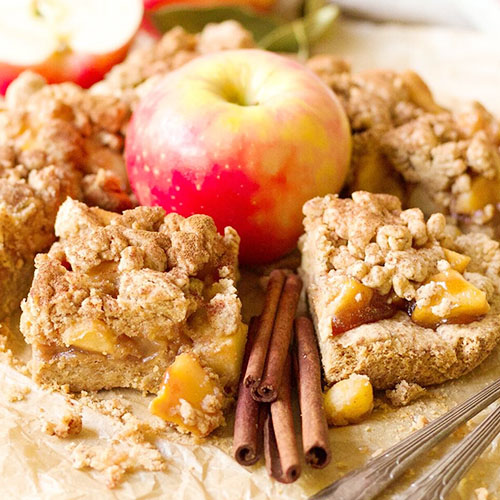 apple pie shortbread bars with an assortment of apples and cinnamon sticks