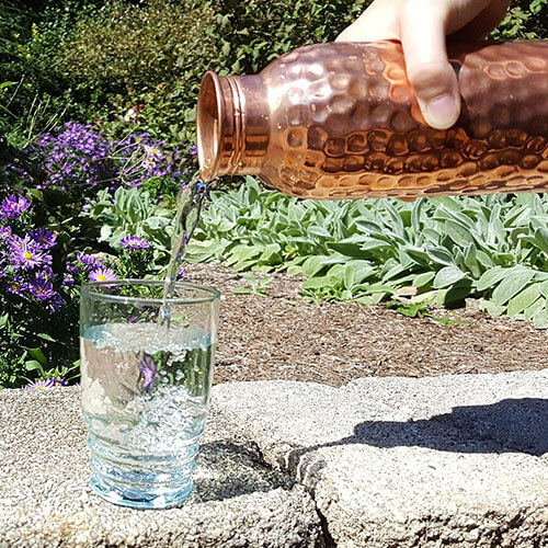hand holding a hammered copper water bottle and pouring water into a glass outside