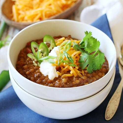 bowl of lentil chili topped with sour cream, grated cheddar, peppers, and cilantro
