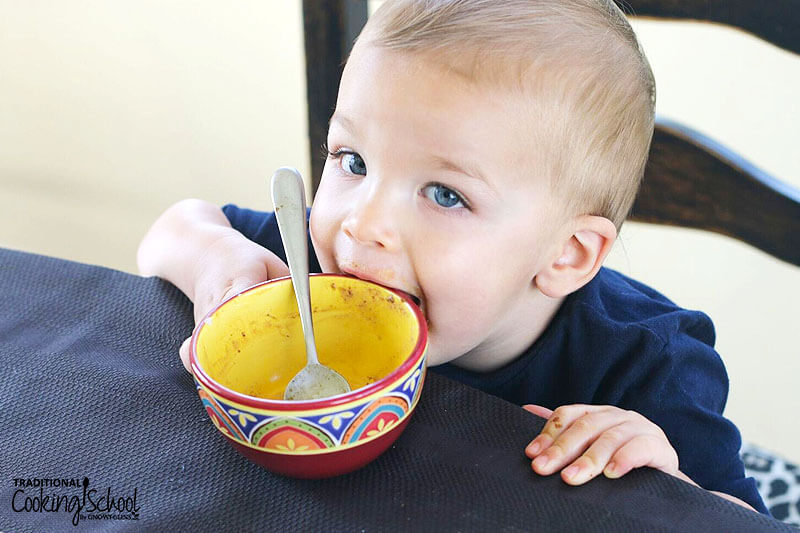 blue-eyed blond toddler tries to eat his empty bowl of gingerbread cookie chunk ice cream