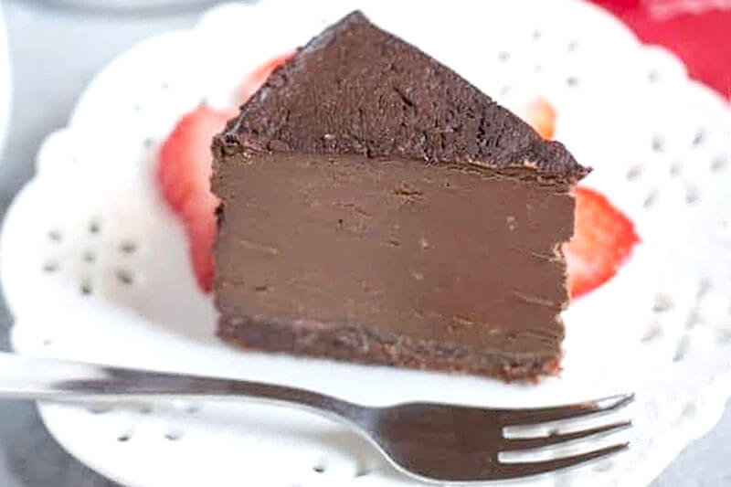 slice of decadent chocolate cheesecake with a fork next to it