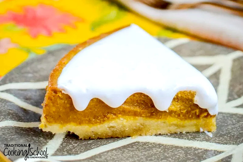 slice of pumpkin pie with homemade whipped cream oozing down the sides