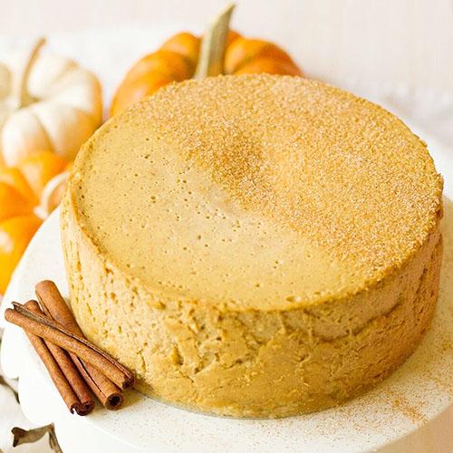 pumpkin cheesecake on a platter next to cinnamon sticks