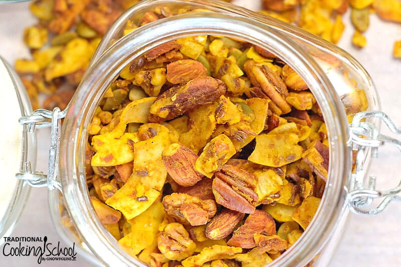 glass jar of pumpkin pie granola with nuts and dried pumpkin pieces