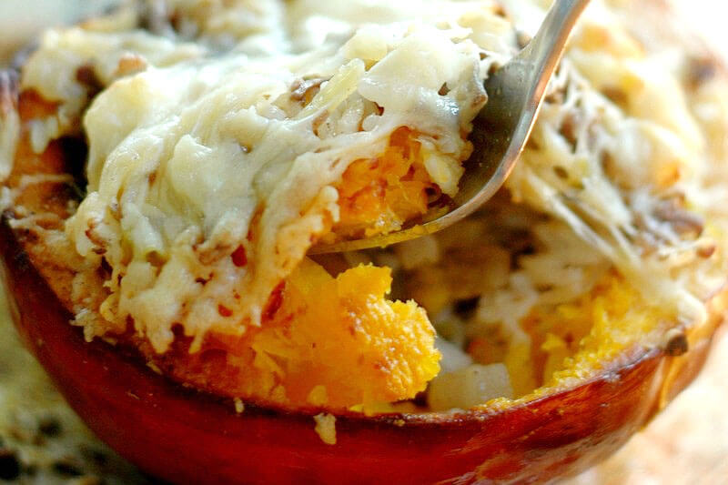 fork scooping into a cheesy stuffed pumpkin