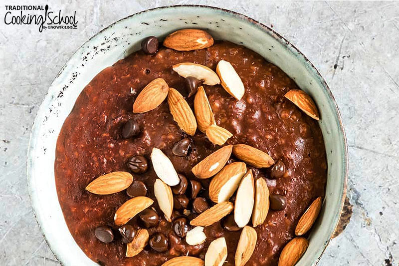big bowl of chocolate oatmeal with almonds and chocolate chips on top