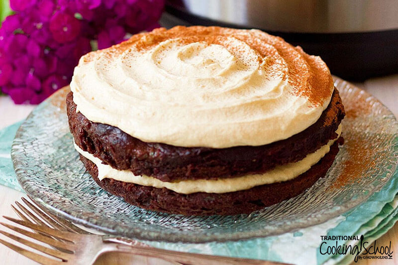 layered chocolate cake with cream cheest frosting sprinkled with cinnamon between the layers and on top
