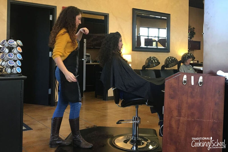 hairdresser giving a woman with dark curly hair a haircut