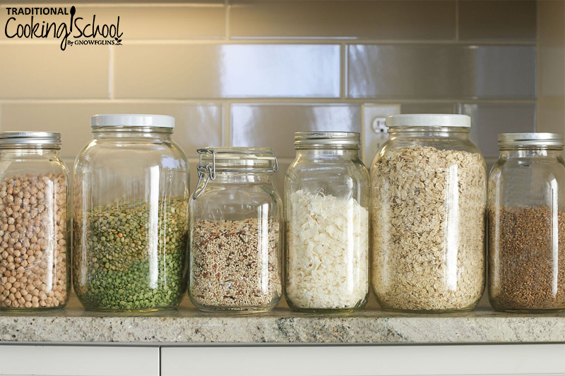 jars of pantry items, including chickpeas, lentils, rice, coconut, and oats, lined up on a counter