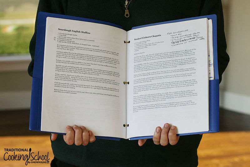 photo of a woman in a green fleece zipper pullover holding open a blue folder of her favorite recipes, including Sourdough English Muffins and Soaked Einkorn Chapatis