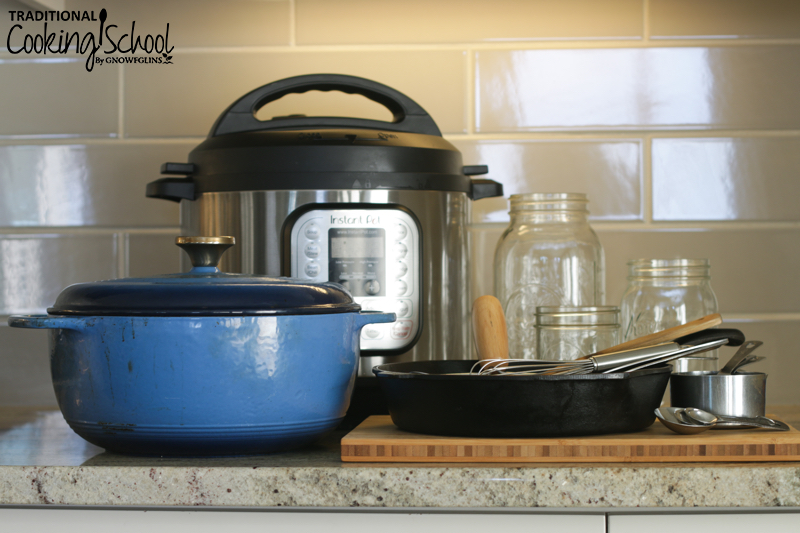 kitchen tools and appliances arranged on a counter, including an Instant Pot, Dutch oven, Mason jars, cast iron skillet, and utensils