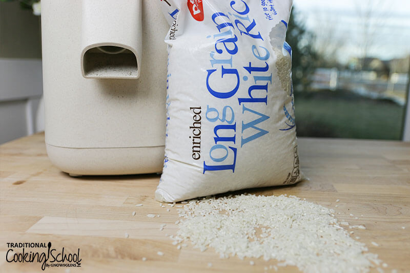 close-up shot of the Mockmill home stone grain mill next to a bag of spilled white rice