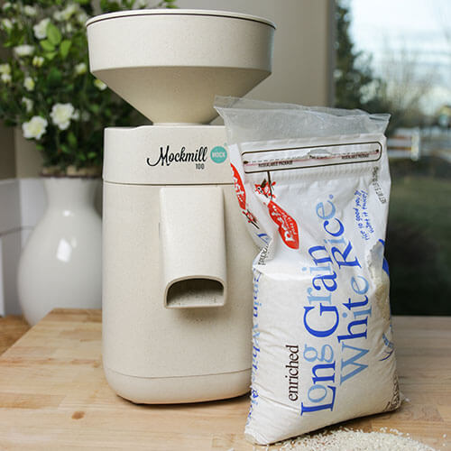 Mockmill home stone grain mill next to a bag of cheap white rice